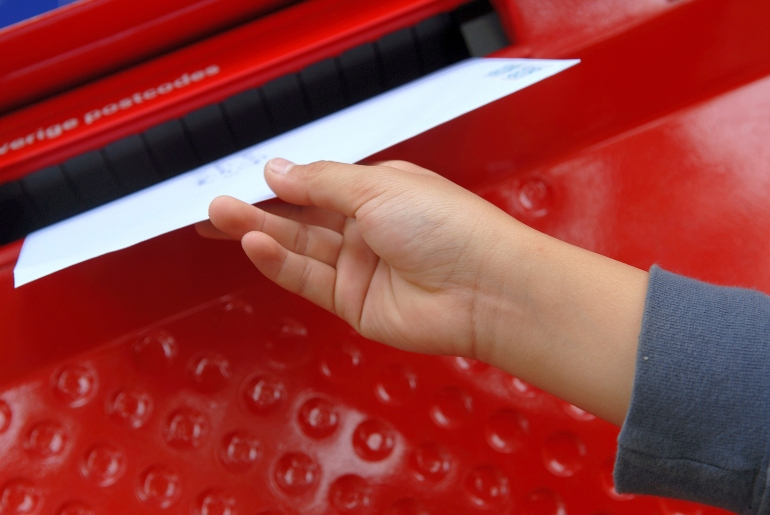 mail into a mail slot-122414163.jpg