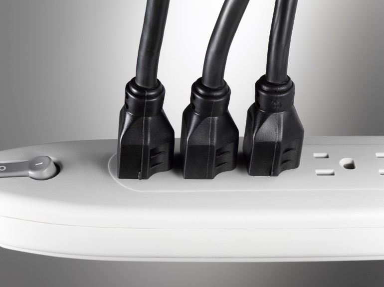 Several extension cords plugged into extension socket, close-up