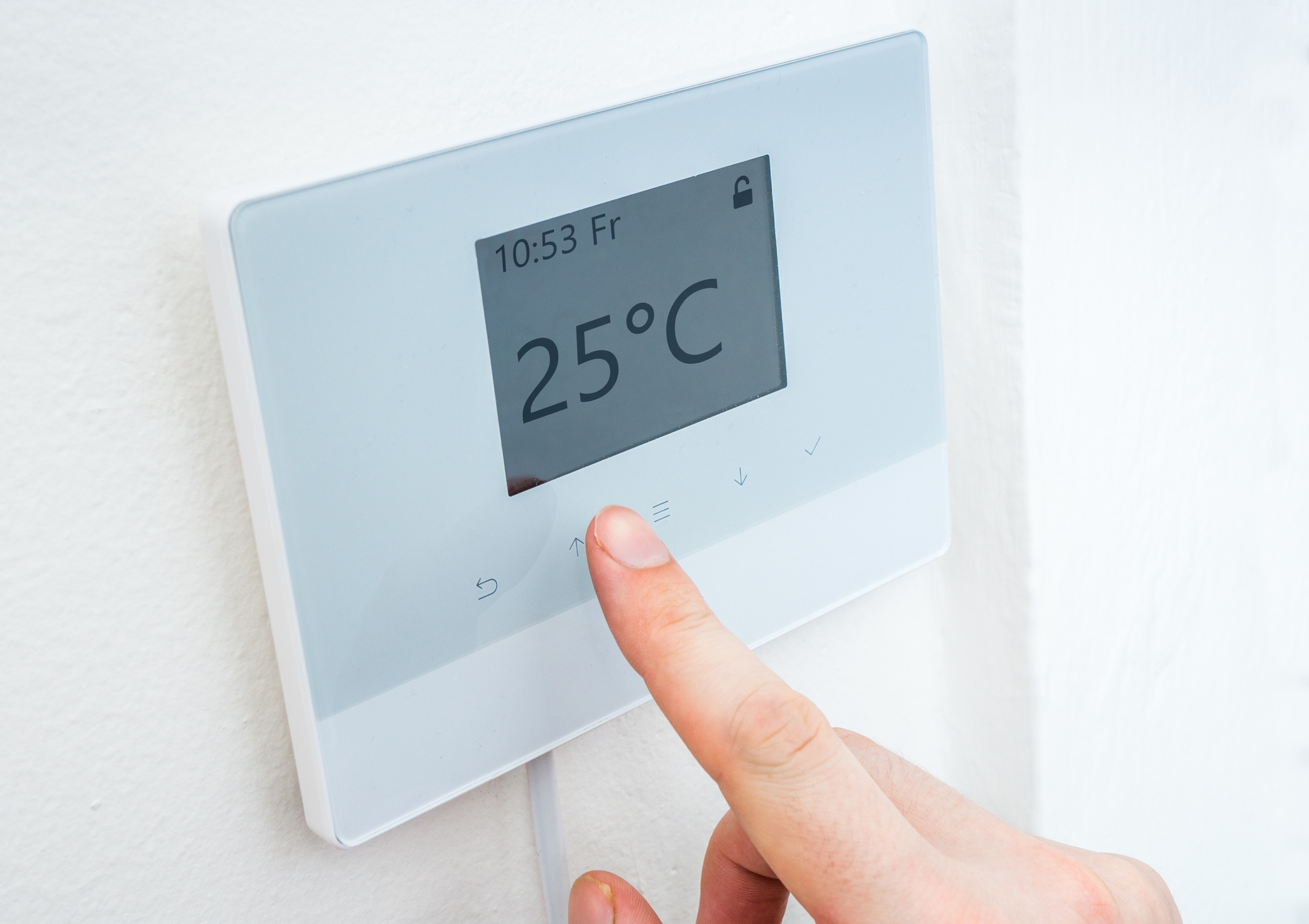 Heating concept. Adjusting temperature on digital central thermostat control.