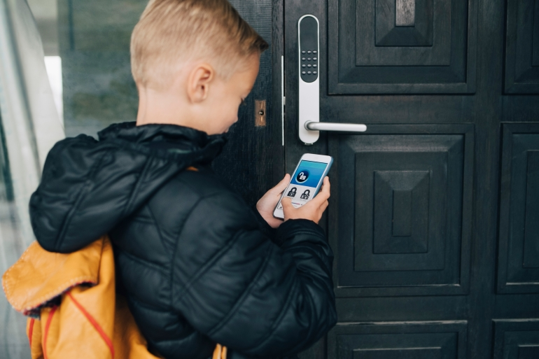 Rear view of boy using app on smart phone to unlock house door