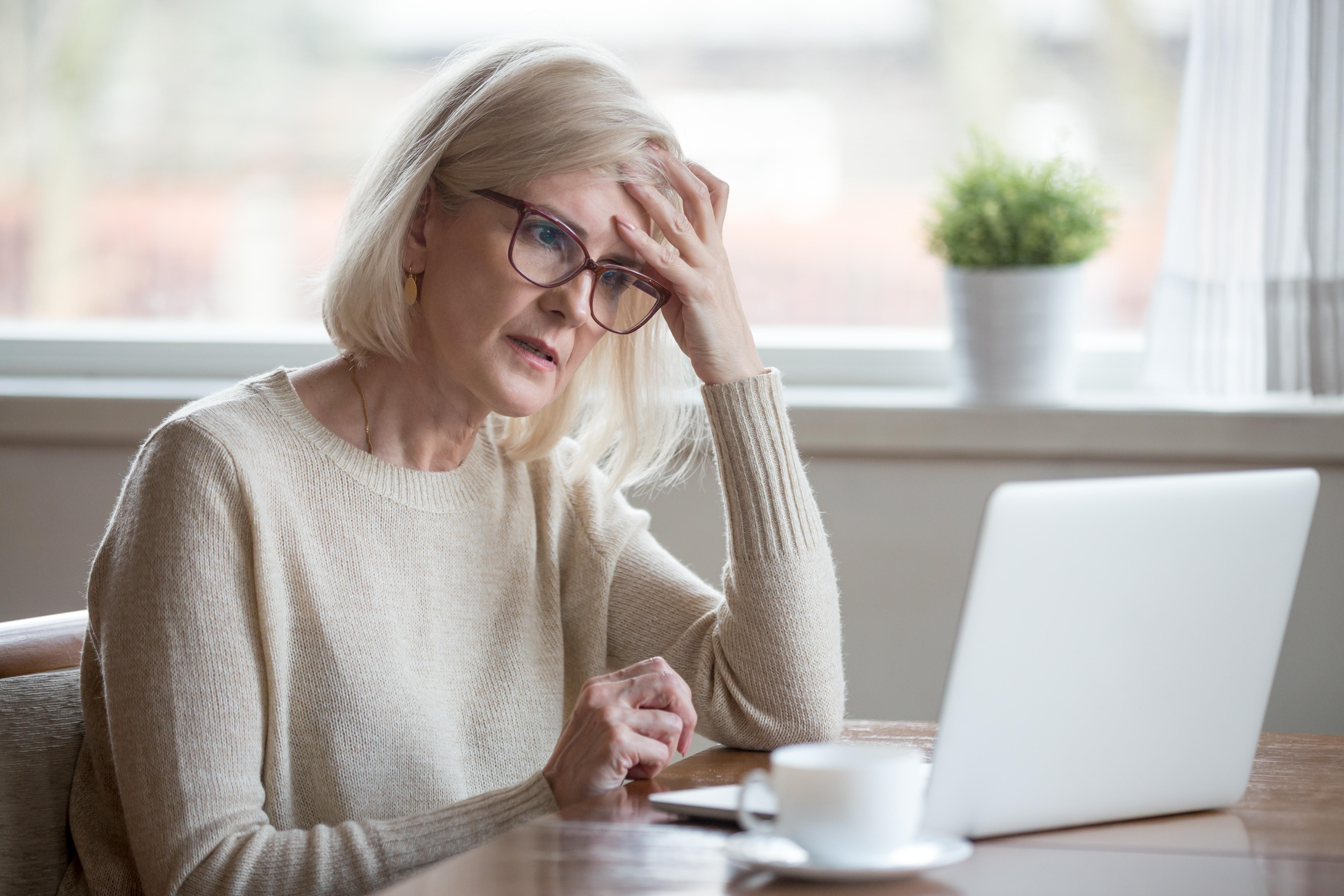 upset woman looking at computer screen